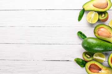 Avocado, kiwi and lime on a wooden background. Top view. Free space for your text.
