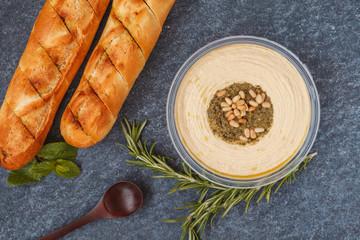 Healthy vegan appetizer, hummus with pine nuts and garlic baguette, dark background