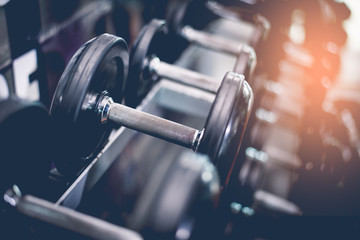 Black steel dumbbell set. Close up of dumbbells on rack in sport fitness center. Workout training and fitness gym concept. Healthy and well being concept. Sport equipment and tool theme.