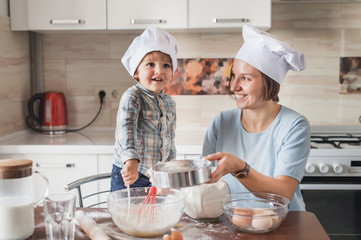 smiling young mother and adorable child preparing dough at kitchen