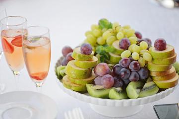 Fresh colorful fruits including grapes kiwi pear white bowl closeup