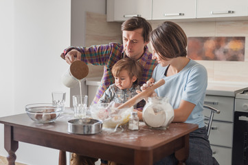 beautiful young family preparing dough at modern kitchen