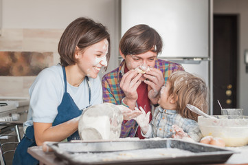 adorable young family having fun with flour at kitchen while baking