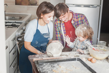 beautiful young family having fun with flour at kitchen while baking