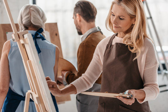 beautiful mature woman holding palette and painting on easel during art class for adults