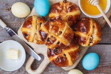 Easter cross buns, painted eggs. Wooden background, copy space, top view. Easter food concept.