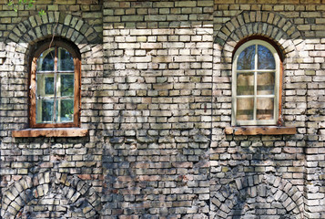 Two blind windows in the yellow ruined brick wall of the old aged no name castle