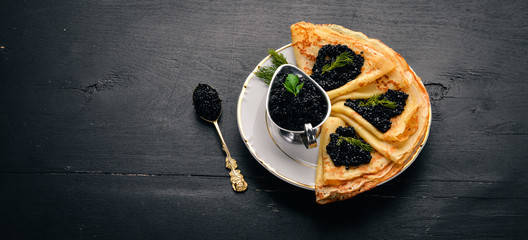 Pancakes with black caviar on a plate. On a wooden background. Top view. Free space for text.