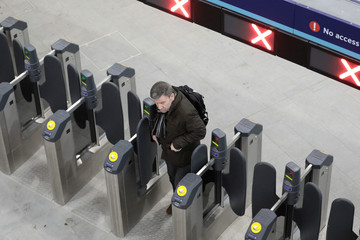 A commuter uses a ticket barrier to enter London Bridge train station in London
