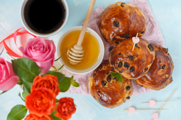 Breakfast for Valentine's Day. Buns with raisins, butter and honey, coffee, bouquet of flowers. Top view, blue background. Valentine's Day concept.