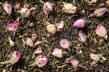 Background with green tea and rose blossom flowers with copy space. Top view.