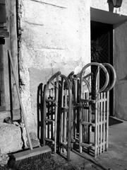Rodelschlitten und Besen aus Holz am Eingang eines Bauernhaus in Rottenbuch in Oberbayern, fotografiert in klassischem Schwarzweiß