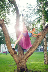 Ballet dancer dancing on street. Young ballerina in purple tutu. Pretty ballerina in the park doing exercise on tree.