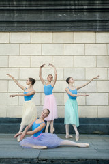 Ballet dancers dancing on street near the theatre. Young ballerinas in color tutus. Ballet feet on the point