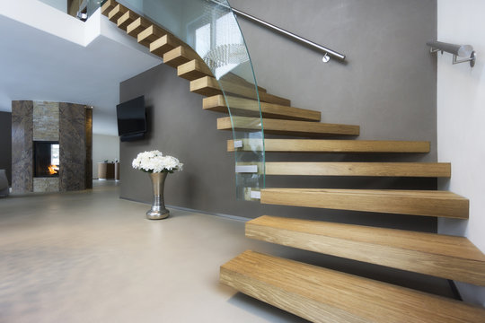 elegant wood and glass staircase in luxury home