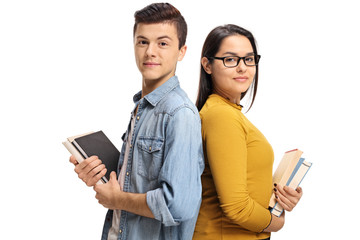 Teenage students with books with their backs against each other