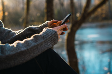 Charming woman browsing smartphone in fall woods