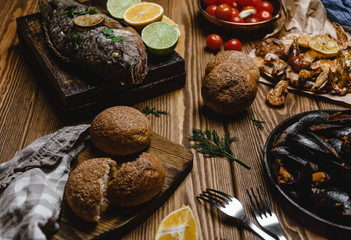 Assorted seafood and baked fish with bread and tomatoes on wooden table