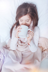 Cozy mood. Upset kid holding big cup in both hands being under soft and warm blanket while drinking tea