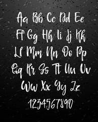 Handwritten brush style modern cursive font isolated on chalkboard background.