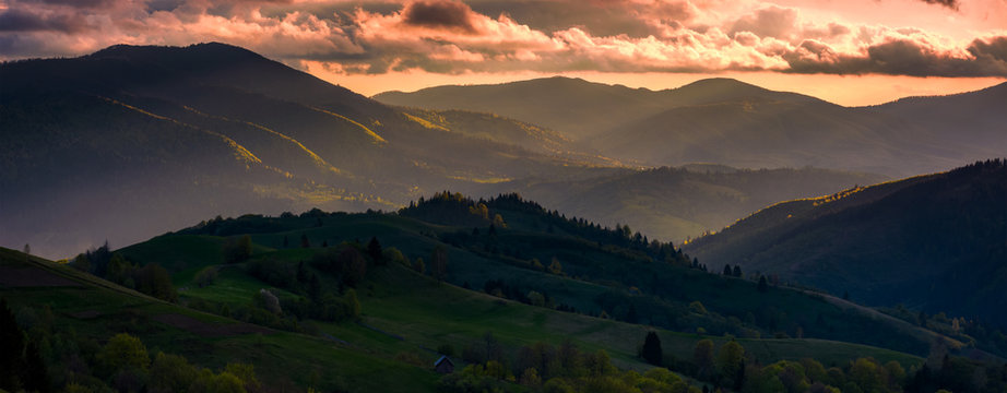 red sunset in mountainous countryside. gorgeous panorama of Carpathian mountains with cloudy sky in springtime