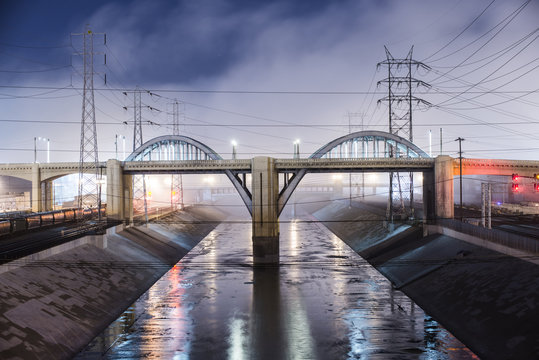 Sixth Street Viaduct over Los Angeles River against cloudy sky at night