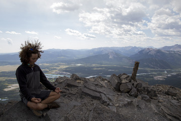 Full length of man meditating while sitting on rock against sky