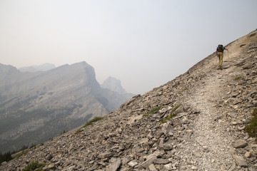 Rear view of hiker climbing on mountain against sky