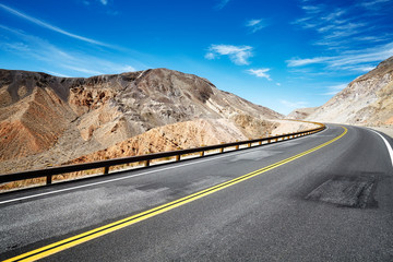 Deserted mountainous terrain with empty highway, travel concept, USA.