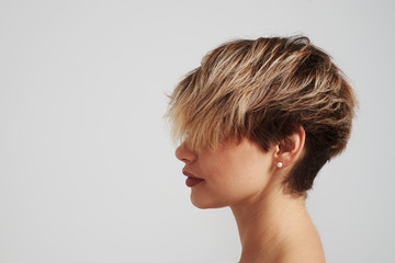 Beautiful blond woman with short hairstyle posing at studio