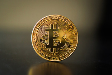 Single bitcoin coin close up on the surface