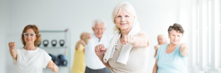 Senior sportswoman exercising with friends
