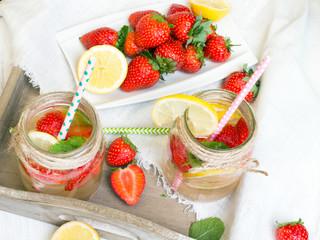 Fototapeta Mineralna woda z dodatkiem świeżych truskawek, cytryny, limonki i mięty. Orzeźwiający napój