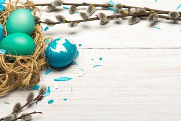 Obraz Tło Wielkanoce  z pisankami, baziami na białym drewnianym tle. Miejsce na tekst - fototapety do salonu