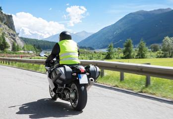 Motorradfahrer fährt mit seinem Motorrad auf kurvigen Straßen durch die Berge und einer wunderschöne Landschaft