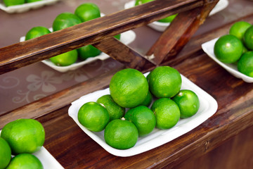 Fresh limes on a wooden table at the street market. Chiang Mai, Thailand.
