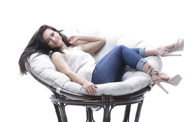 modern young woman relaxing in a round cozy soft chair.