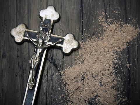 Krzyż i rozsypany popiół jako symbole Środy Popielcowej. Święto rozpoczynające Wielki Post.