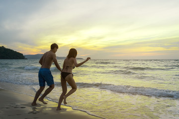 Asian couple holding hand together and running on beach to the sea with bikini and evening light. Relax and traveling at sea concpet.