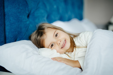 Sweet little girl before sleeping or wake up with smile in her bed at home, close up