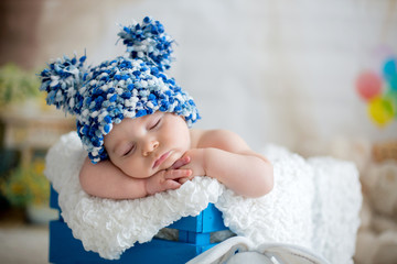 Little baby boy with knitted hat, sleeping with cute teddy bear