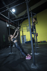 Women training olympic ring in crossfit room