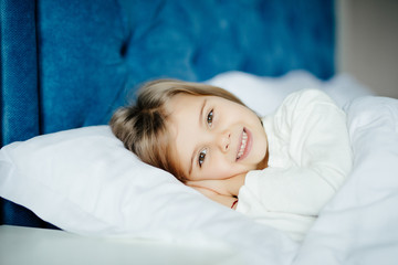 health and beauty concept - little girl sleeping at home with smile in her bed