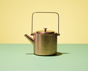 Copper tea kettle with yellow background
