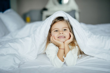 Pretty little girl in sleepwear lying under blanket at home