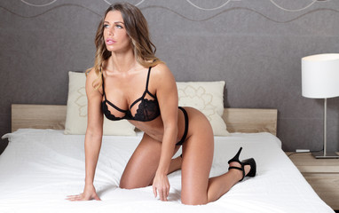 Sexy black lingerie woman with fitness body on bed