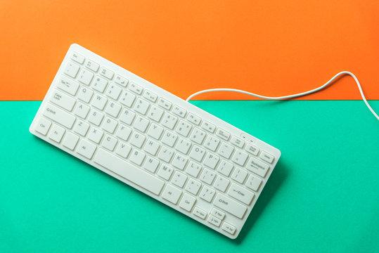 white computer keyboard on orange green background