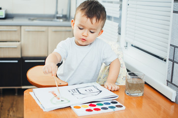 Charming baby in a child seat, draws and
