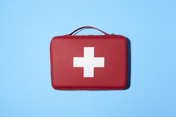 Red medical kit isolated on blue background