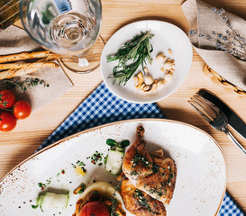 beautifully served roasted quail with mashed potatoes and mushrooms with a glass of water, Italian grissini sticks and a bottle of olive oil on a wooden table